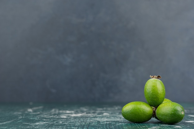 Zielone owoce feijoa na marmurowej powierzchni.