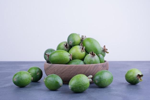 Zielone owoce feijoa w drewnianym kubku na niebieskim stole.