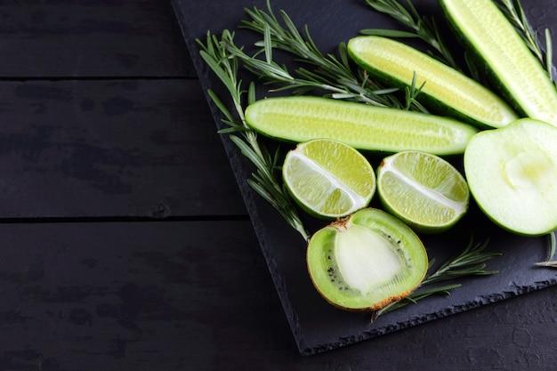 Zielone owoce, warzywa i rozmaryn. kreatywna postać naturalnych zielonych produktów. ogórki, kiwi, limonka i zielone jabłko na desce łupkowej