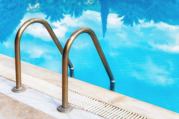 Zielone palmy odbijają się na nowoczesnym odkrytym luksusowym basenie z lazurową wodą