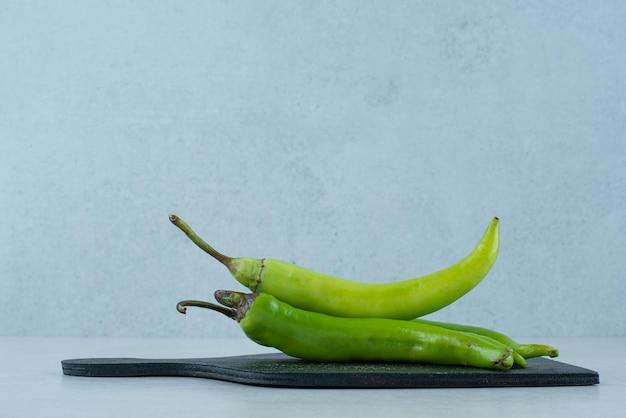 Zielone papryczki chili na ciemnej desce.