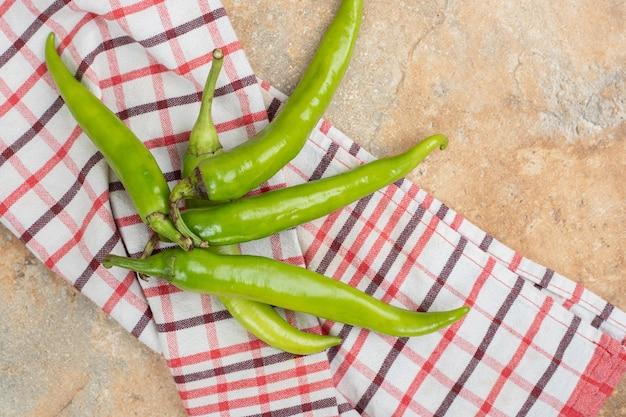 Zielone papryczki chili na obrusie na marmurowej powierzchni.