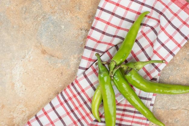 Zielone papryczki chili na obrusie na marmurowej powierzchni