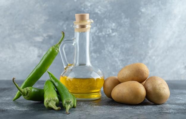 Zielone papryczki chili, oliwa z oliwek i ziemniaki na marmurowym tle