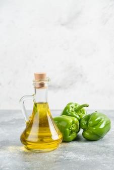 Zielone papryczki chili z butelką oliwy z oliwek z pierwszego tłoczenia na marmurowym stole.