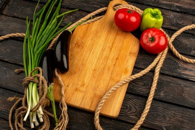 Zielone papryki świeże dojrzałe czarne bakłażany czerwone pomidory wraz z zielenią na brązowej drewnianej rustykalnej podłodze