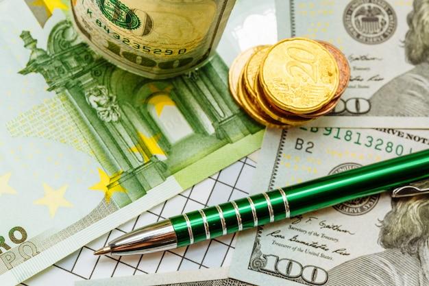 Zielone pióro leży na banknotach dolarowych w pobliżu złotych monet na stole.