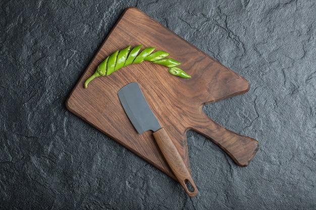 Zielone plasterki papryczki chili na drewnianą deskę do krojenia. wysokiej jakości zdjęcie