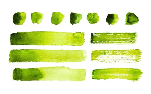 Zielone pociągnięcia akwarelą i plamy na białym tle