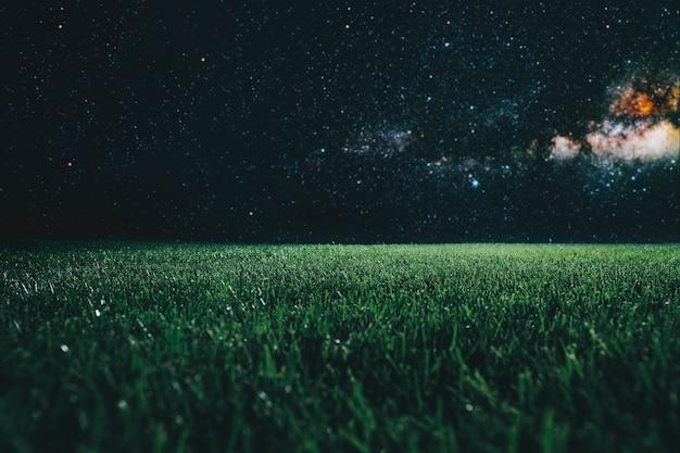 Zielone pole na tle nocnego nieba. elementy tego obrazu dostarczone przez nasa