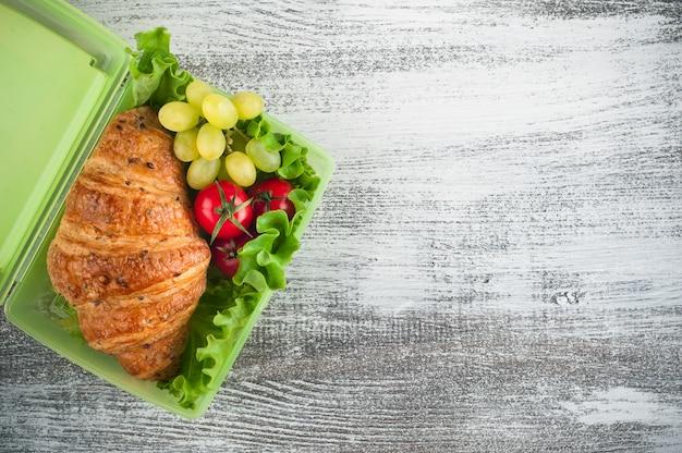 Zielone pudełko na lunch z rogalikiem, sałatką