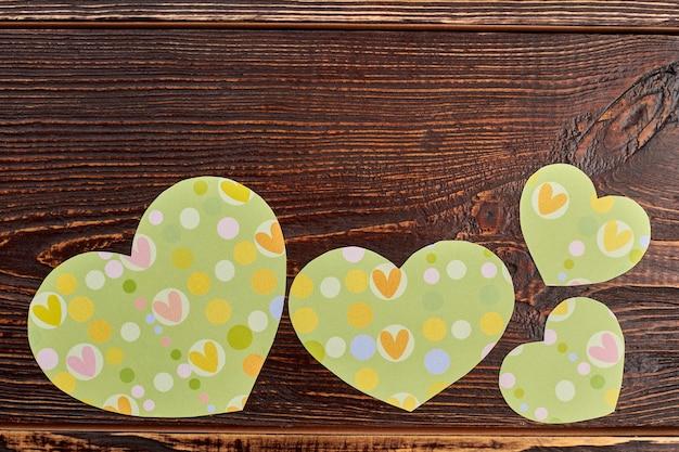 Zielone serca księgi na brązowym drewnie. dekoracje papierowe w kształcie serca na ciemnym drewnie teksturowanym, miejsce na kopię.