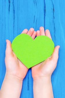 Zielone serce w rękach dziecka