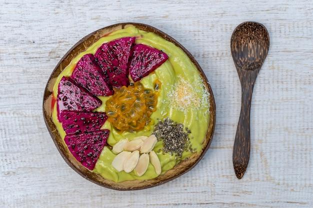 Zielone smoothie z awokado w kokosowej misce z owocem smoka, marakuja, płatki migdałów, chipsy kokosowe