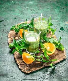 Zielone smoothie z warzywami, owocami i miętą. na tle rustykalnym.