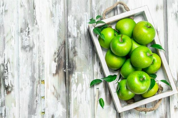 Zielone soczyste jabłka w całości w drewnianym pudełku. na białej drewnianej powierzchni.