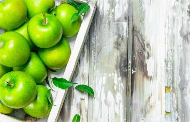 Zielone soczyste jabłka w całości w drewnianym pudełku.