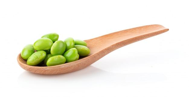 Zielone soje w drewnianej łyżce na bielu stole