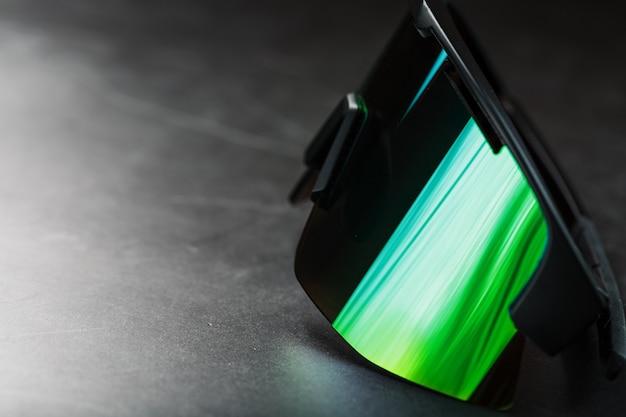 Zielone sportowe okulary z lustrzanymi soczewkami na ciemnej powierzchni
