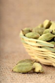 Zielone strąki kardamonu w bambusowym koszu na worek szmatką