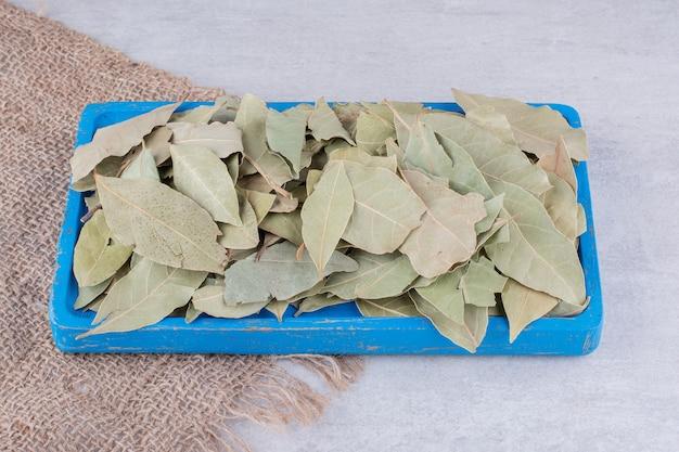 Zielone suche liście laurowe na betonowej powierzchni