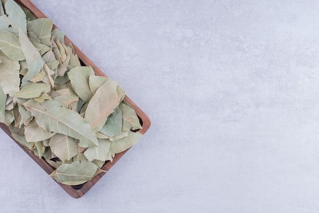 Zielone suche liście laurowe na drewnianym półmisku