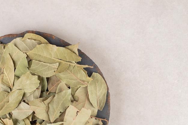 Zielone suszone liście laurowe na drewnianym talerzu.