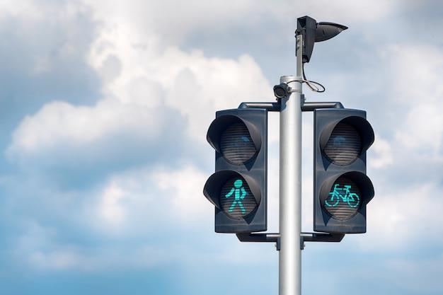 Zielone światła dla rowerów i pieszych, zielone światła dla rowerów dają pierwszeństwo rowerzystom, piesi przekraczają światła na tle miasta.