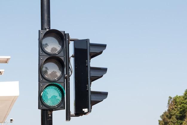 Zielone światła drogowe, na białym tle na niebie