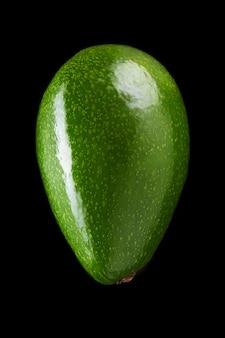 Zielone świeże awokado na czarnym tle z bliska