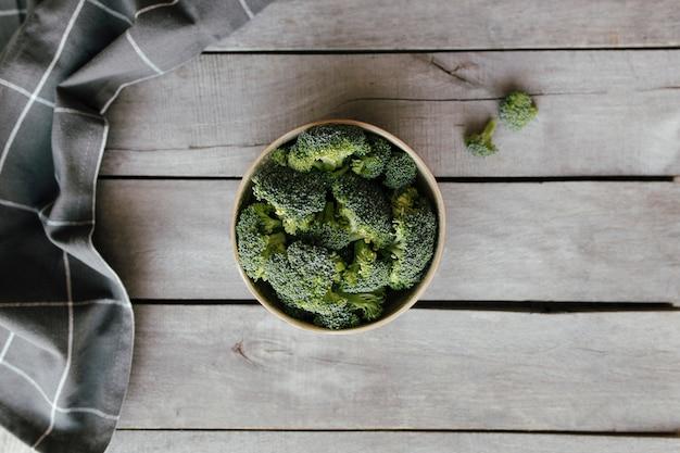 Zielone świeże brokuły w misce na podłoże drewniane, szary ręcznik. koncepcja zdrowego odżywiania.
