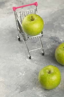 Zielone świeże jabłka w metalowym koszyku na marmurze.
