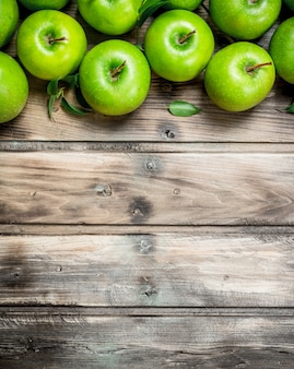 Zielone świeże jabłka z liśćmi. na szarym drewnianym.