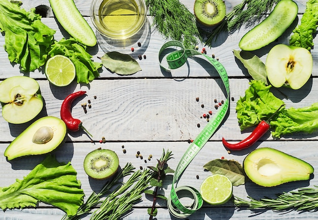 Zielone świeże warzywa i przyprawy na białym drewnianym stole. widok z góry. miejsce na tekst
