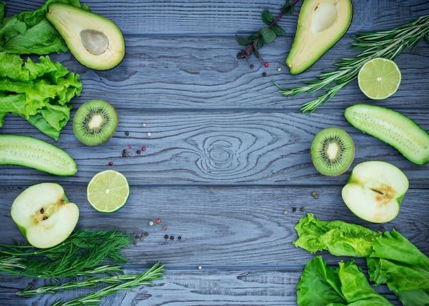 Zielone świeże warzywa i przyprawy na niebieskim drewnianym stole. widok z góry. miejsce na tekst