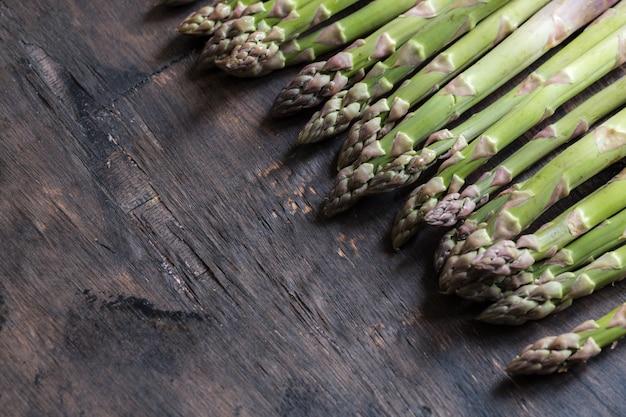 Zielone szparagi. wiązki zielonych szparagów na ciemnym drewnianym tle rustykalnym