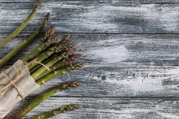 Zielone szparagi. wiązki zielonych szparagów na niebieskim tle drewnianych rustykalne