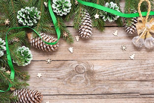 Zielone szyszki z gałęzi jodłowych na starym drewnianym stole. w dzień bożego narodzenia.