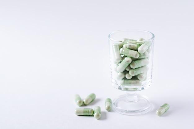 Zielone tabletki kapsułki w kieliszku koktajlowym na białym tle