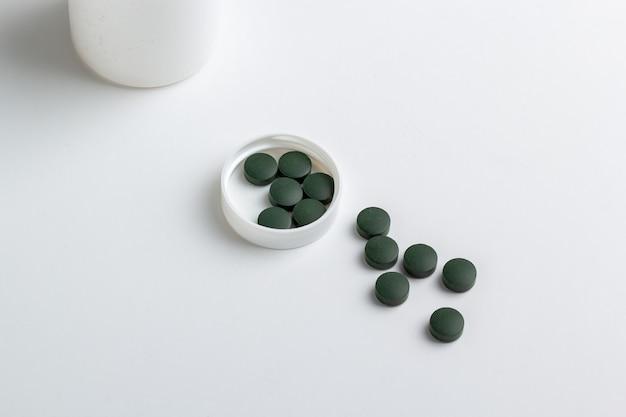 Zielone tabletki na białym tle na białym tle