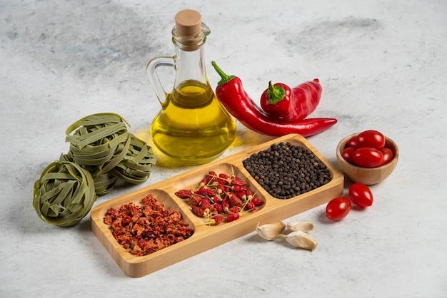 Zielone tagliatelle, suszone przyprawy i oliwa z oliwek na marmurowym tle.