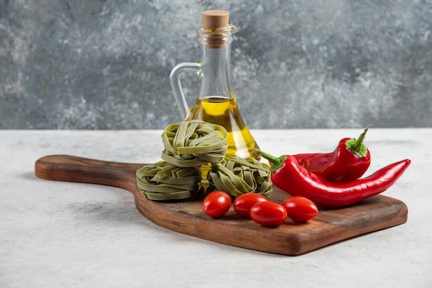 Zielone tagliatelle, warzywa i oliwa z oliwek na desce.