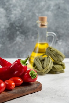 Zielone tagliatelle, warzywa i oliwa z oliwek na tle marmuru.