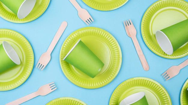 Zielone talerze z kubkami i sztućcami leżą płasko