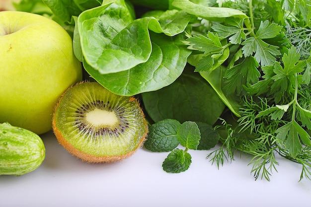 Zielone warzywa jabłko, szpinak, kiwi, ogórek, pietruszka, koperek i mięta. składniki do koktajli
