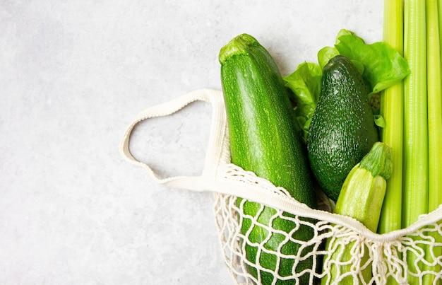 Zielone warzywa w worek strunowy na tle marmuru.