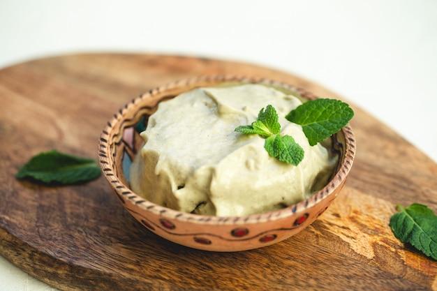 Zielone wegańskie lody domowej roboty z awokado lub lody pistacjowe z listkami mięty.