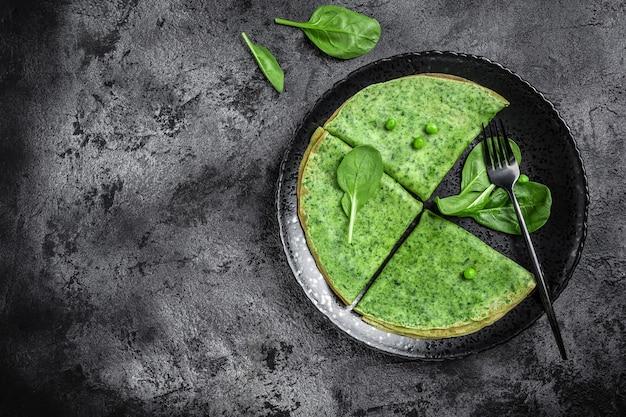 Zielone wegańskie naleśniki ze szpinakiem na ciemnym tle. zdrowe śniadanie, wegetariańskie jedzenie, baner, miejsce na przepis menu dla tekstu, widok z góry.
