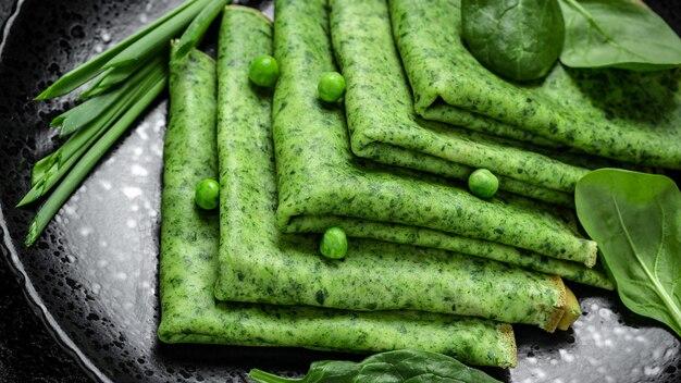 Zielone wegańskie naleśniki ze szpinakiem na czarnej płycie, ciemne tło, zdrowe śniadanie, wegetariańskie jedzenie, widok z góry.