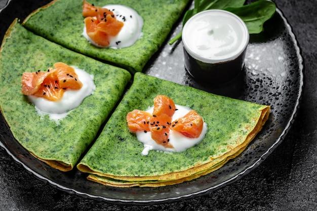 Zielone wegańskie naleśniki ze szpinakiem, wędzonym łososiem i sosem jogurtowym, zdrowe śniadanie, wegetariańskie jedzenie, widok z góry.
